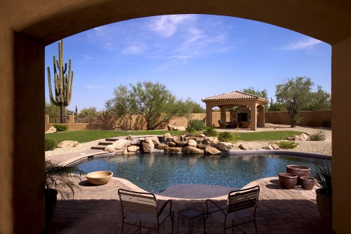 Backyard with swimming pool framed by a cover arched patio.